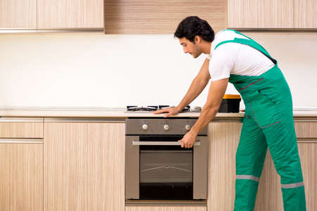 Young contractor repairing oven in kitchen 스톡 콘텐츠