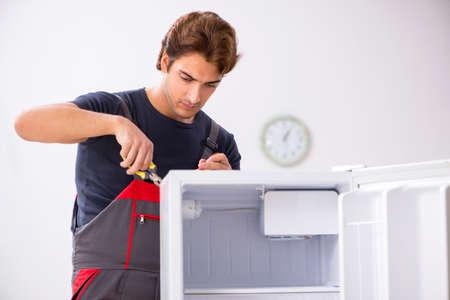 Young handsome contractor repairing fridge Фото со стока