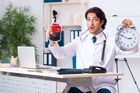 Young handsome doctor in blood transfusion concept