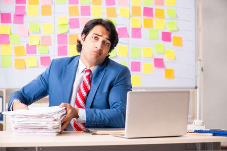 Young handsome employee with many conflicting priorities Banque d'images