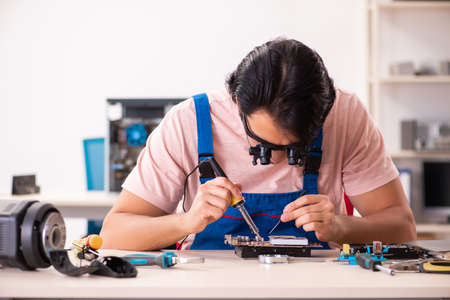 Young male contractor repairing computer Archivio Fotografico