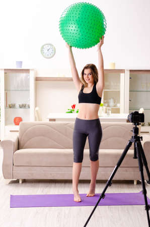 Young beautiful girl blogger doing exercises at home 写真素材 - 118569283