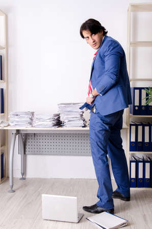 Young businessman employee unhappy with excessive work Archivio Fotografico