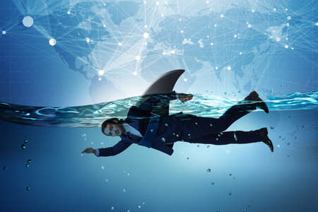 Businessman with shark fin swimming in water