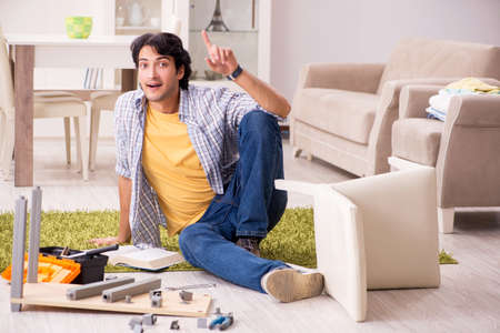 Young handsome man repairing chair at home