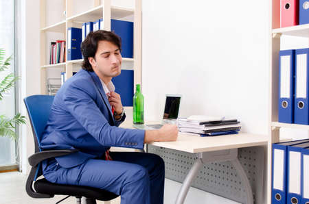 Young businessman employee drinking in the office Stock Photo