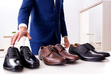 Young handsome businessman choosing shoes at home Foto de archivo