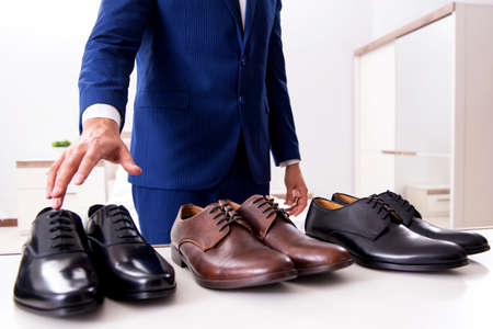 Young handsome businessman choosing shoes at home Фото со стока