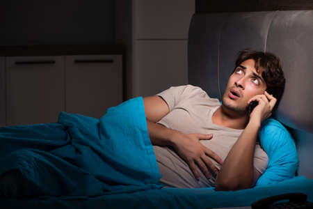 Young man talking on mobile late at night Stock Photo