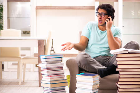 Male student with many books at home