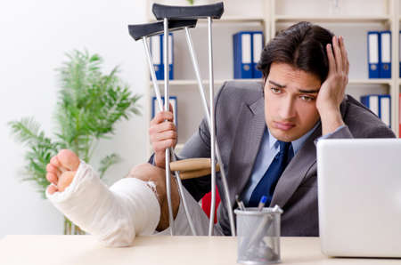 Leg injured employee working in the office Imagens