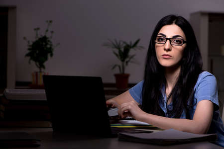 Young female student preparing for exams at night time Stock Photo