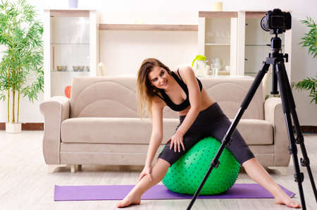 Young beautiful girl blogger doing exercises at home