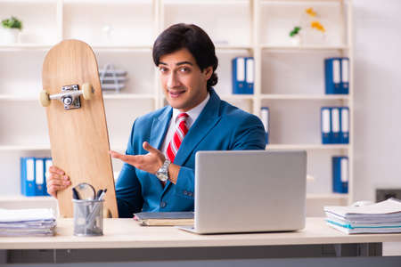 Young handsome businessman with longboard in the office Imagens