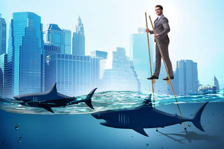 Businessman walking on stilts among sharks
