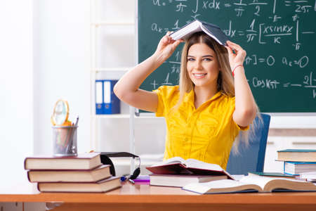 Young female student in front of the chalkboard