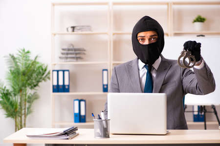 Male gangster stealing information from the office Imagens