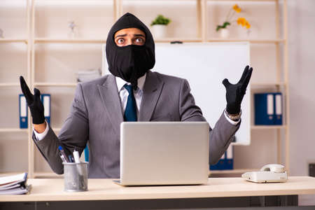 Male gangster stealing information from the office Stock Photo - 119295968