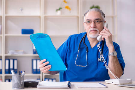 White bearded old doctor working in clinic