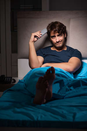 Man watching tv at night in bed