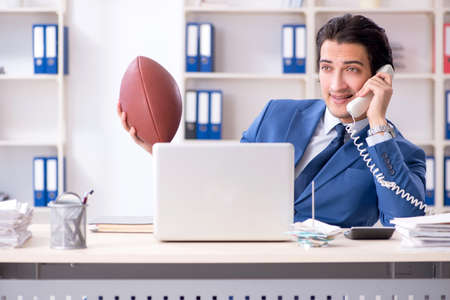 Young handsome businessman with rugby ball in the office