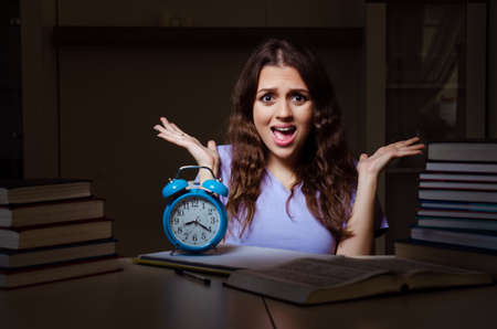Young female student preparing for exams late at home