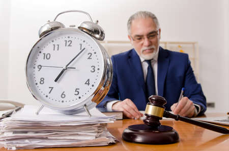 Aged lawyer working in the courthouse Stockfoto