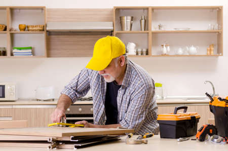 Aged contractor repairman working in the kitchen
