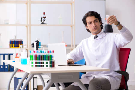 Young handsome chemist working in the lab Stok Fotoğraf