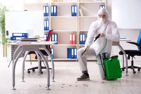 Entrepreneur professionnel faisant la lutte antiparasitaire au bureau Banque d'images