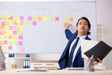 Young handsome employee in front of whiteboard with to-do list