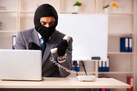 Male gangster stealing information from the office Stock Photo - 119902529
