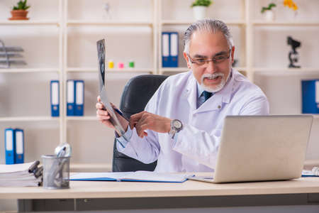 Aged male doctor radiologist in the clinic