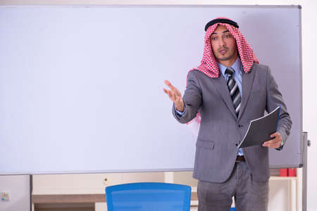Young handsome arab teacher wearing suit