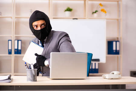 Male gangster stealing information from the office Stock Photo