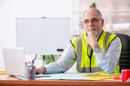 Aged construction engineer working in the office 免版税图像