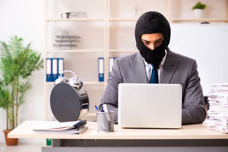 Male gangster stealing information from the office Stock Photo - 119901685