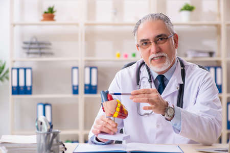 Aged male doctor cardiologist with heart model