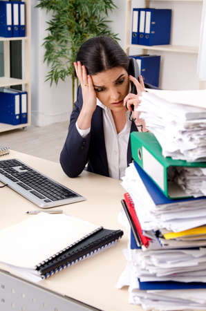 Female employee with too much work in the office Фото со стока