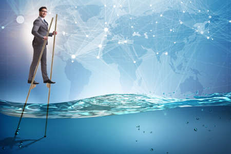 Businessman walking on stilts in water sea