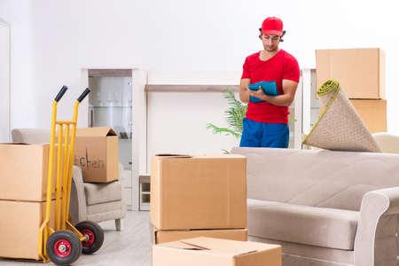 Contratista de sexo masculino joven con cajas trabajando en interiores