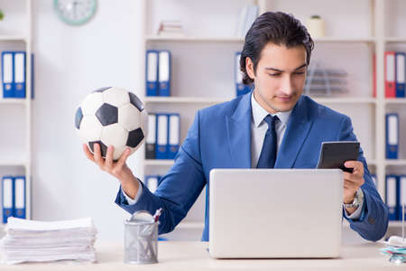 Young handsome businessman with soccer ball in the office Banco de Imagens - 120211463