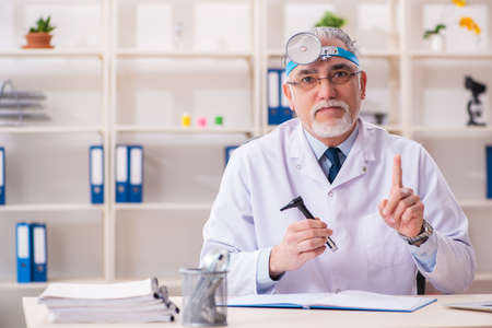 Aged male doctor laryngologist working in the clinic