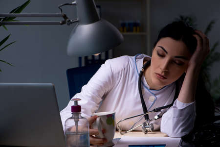 Young female doctor working at night shift Stock Photo