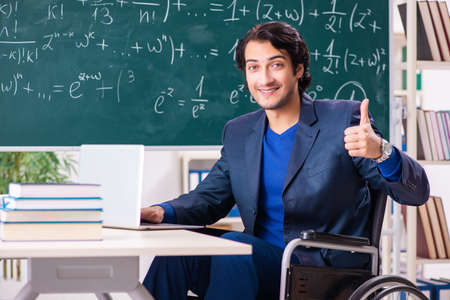 Young handsome man in wheelchair in front of chalkboard
