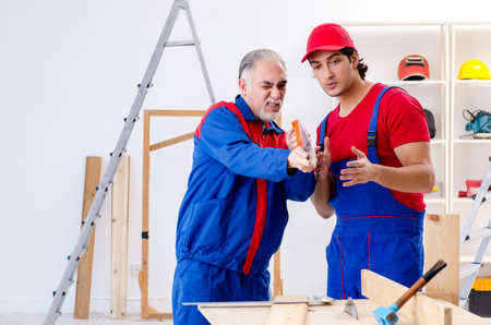 Two professional contractors laying flooring at home Stockfoto