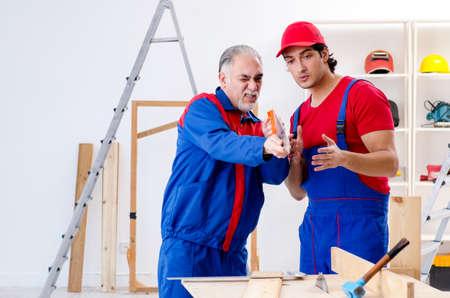 Zwei professionelle Bauunternehmer, die zu Hause Bodenbeläge verlegen Standard-Bild