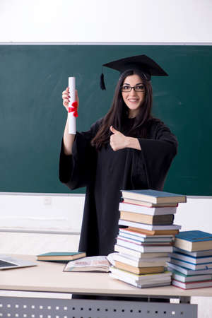 Female graduate student in front of green board Stock Photo