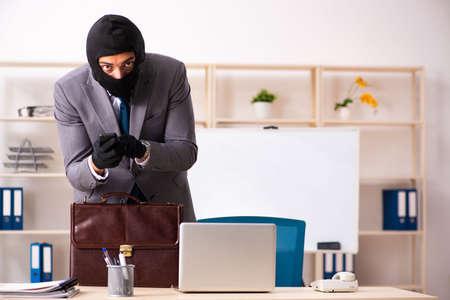 Gángster masculino robando información de la oficina. Foto de archivo