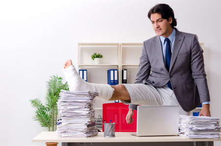 Leg injured employee working in the office Banco de Imagens
